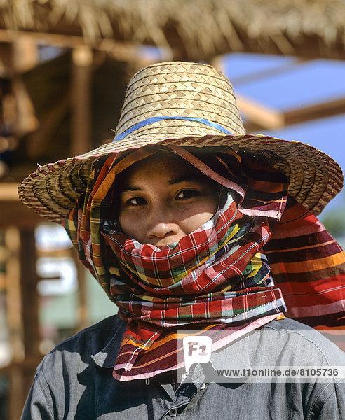 Arbeiterin blickt durch die Öffnung eines Kopftuches  Sonnenschutz  Strohhut  verdecktes Gesicht