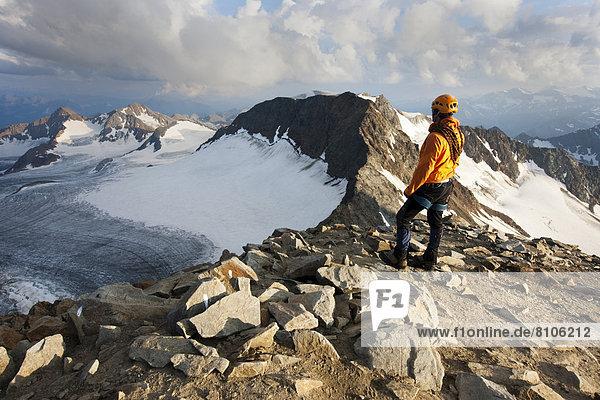 Bergsteiger steht am Gipfel des Wilden Pfaff und blickt Richtung Südtirol