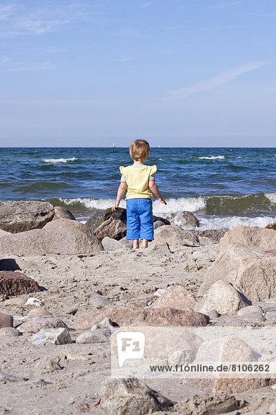 Kleines Mädchen steht am Meer