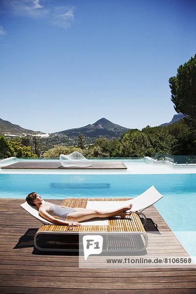 Frau beim Sonnenbaden am Pool