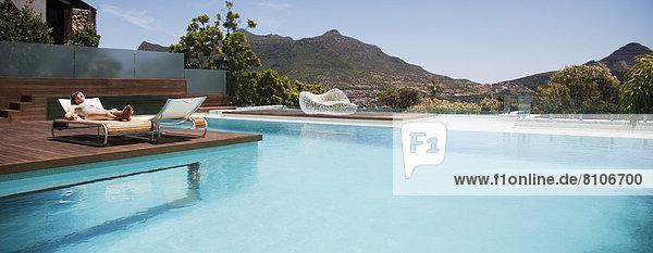 Frau beim Sonnenbaden auf einem Liegestuhl neben dem Luxusschwimmbad mit Bergblick