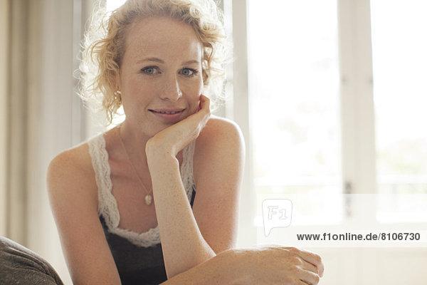 Porträt einer lächelnden Frau mit Kopf in den Händen