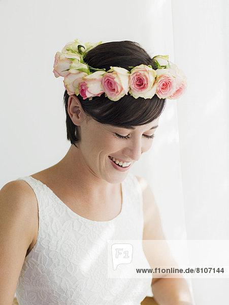 Lächelnde Braut mit Rosenkranz auf dem Kopf