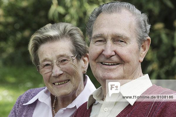 Deutschland  Köln  Porträt eines älteren Paares im Park  lächelnd