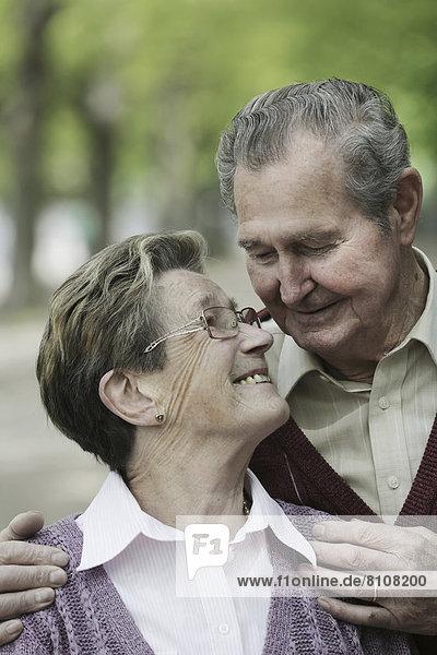 Deutschland  Köln  Seniorenpaar  die sich im Park anschauen  lächelnd