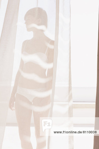 Frau in BH und Unterwäsche hinter sonnigem Vorhang Frau in BH und Unterwäsche hinter sonnigem Vorhang
