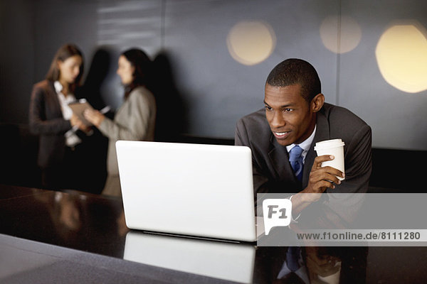 Lächelnder Geschäftsmann trinkt Kaffee und benutzt Laptop