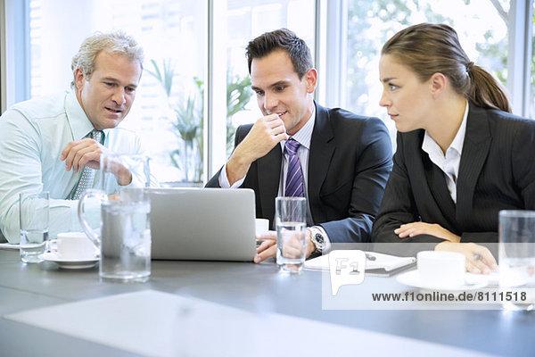 Business-Leute teilen Laptop in der Sitzung