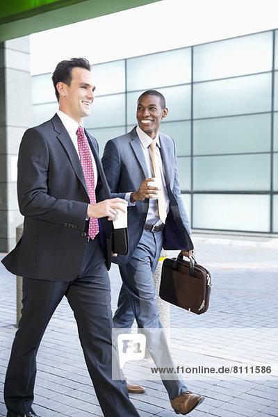 Lächelnde Geschäftsleute  die mit Kaffee spazieren gehen