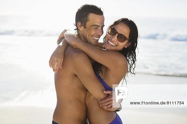 Porträt eines glücklichen Paares  das sich am Strand umarmt.