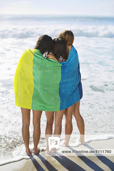 Freunde in Handtuch eingewickelt am Strand