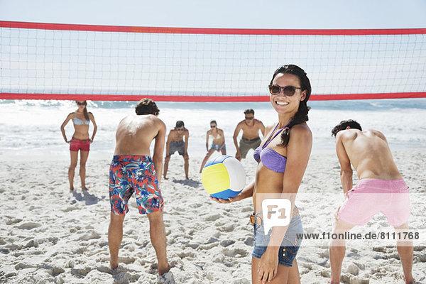Porträt einer lächelnden Frau beim Beachvolleyball mit Freunden