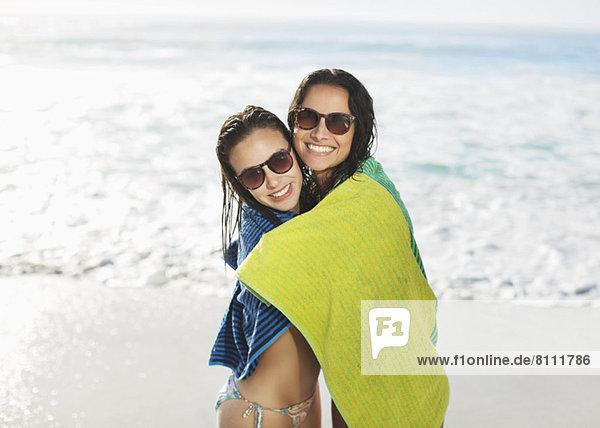 Portrait von lächelnden Freunden in Handtuch gewickelt am Strand