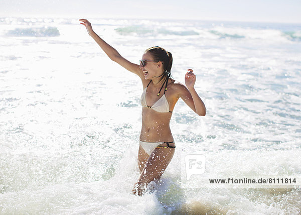 Enthusiastische Frau beim Planschen im Meer