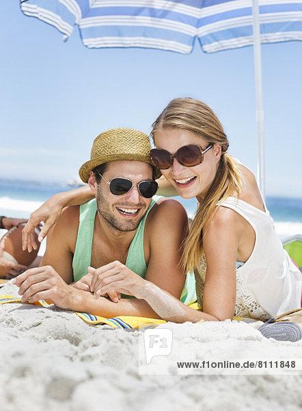 Porträt eines lächelnden Paares am Strand liegend