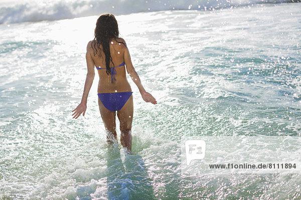 Frau im Bikini waten im Meer