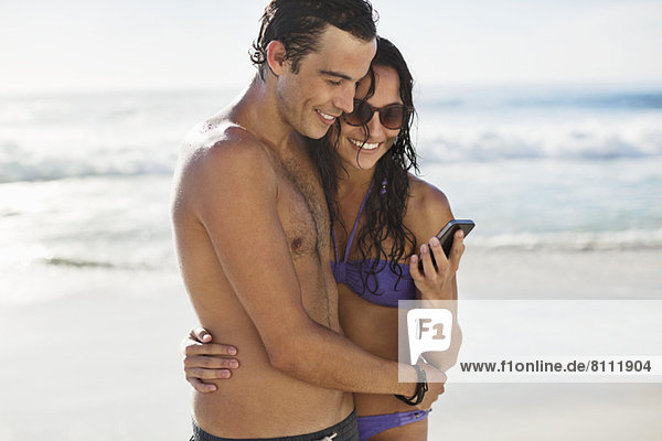 Glückliches Paar mit Handyumarmung am Strand