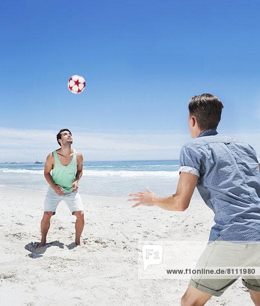 Mann auf dem Weg zum Fußball am Strand