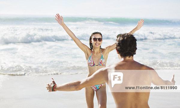 Paar mit ausgestreckten Armen am Strand