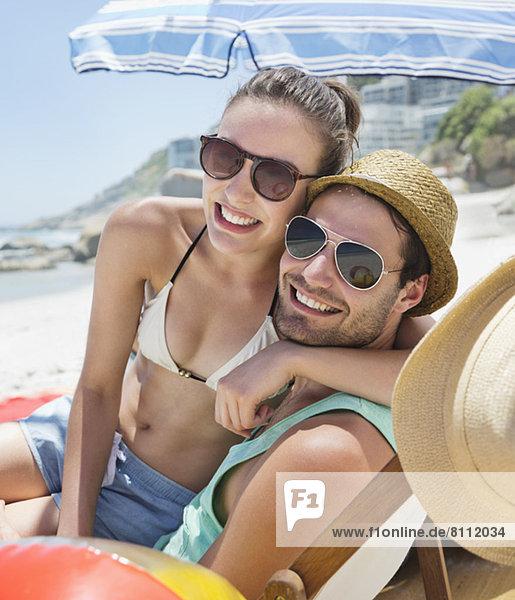 Porträt eines lächelnden Paares mit Sonnenbrille am Strand