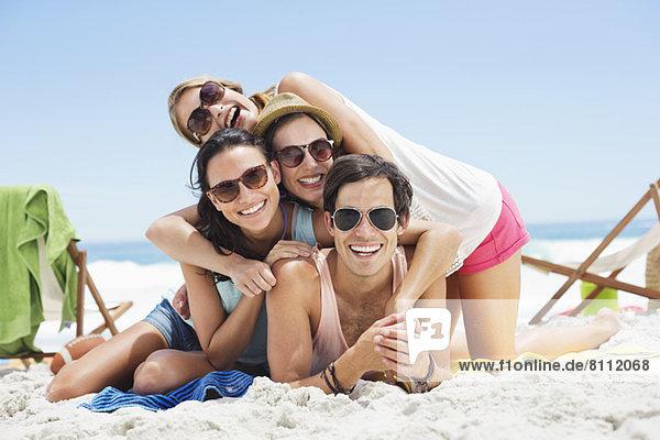 Porträt von glücklichen Freunden  die am Strand übereinander liegen