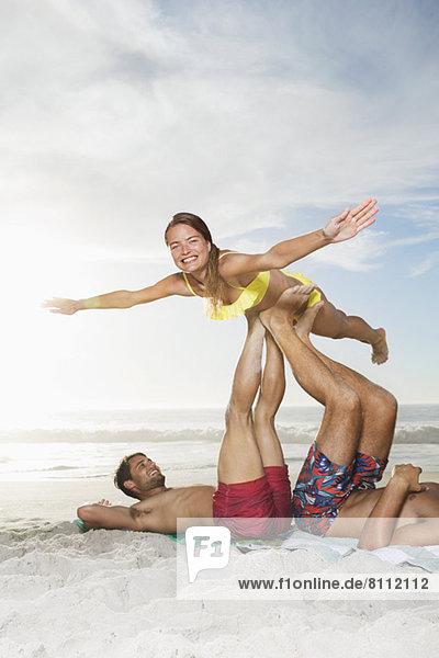 Männer  die Frau mit Beinen am Strand heben