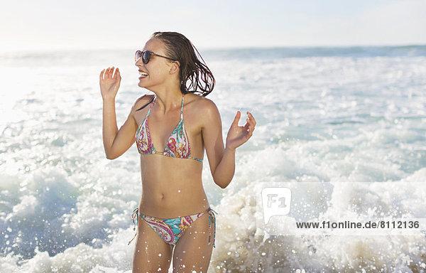 Glückliche Frau im Bikini  die im Meer plätschert.