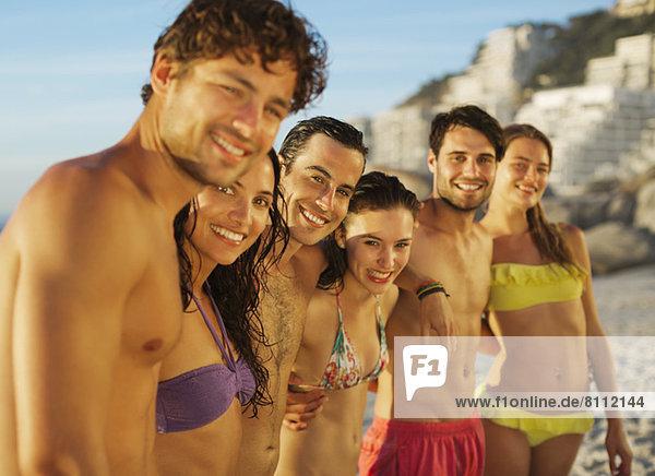 Portrait von glücklichen Freunden in einer Reihe am Strand