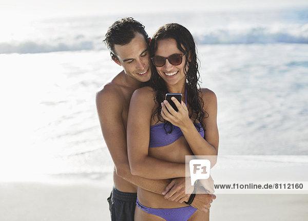 Ein glückliches Paar umarmt sich und schaut sich das Handy am Strand an.