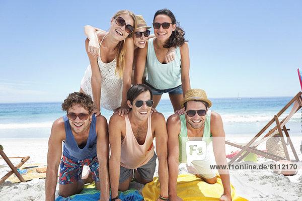 Porträt von glücklichen Freunden  die am Strand eine Pyramide bilden