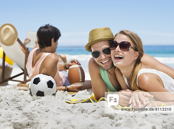 Portrait of smiling couple laying on beach