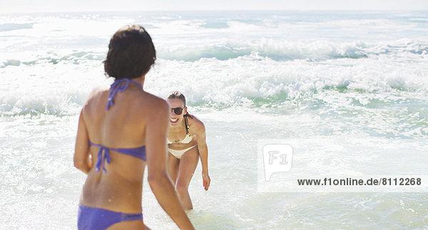 Glückliche Freunde in Bikinis beim Spielen im Meer