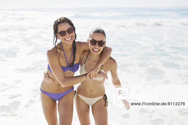 Porträt von begeisterten Freunden in Bikinis am Strand
