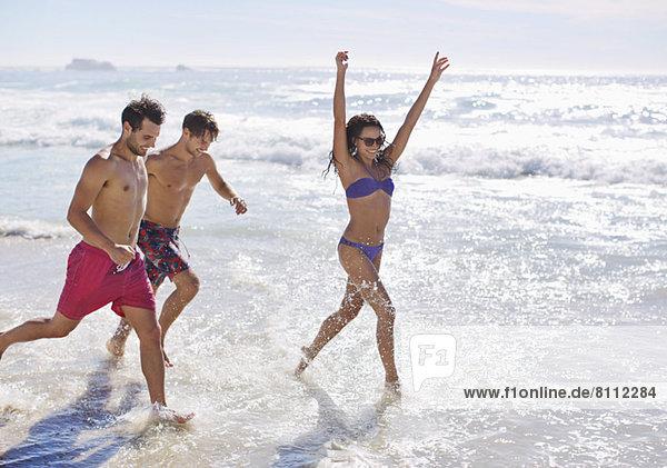 Begeisterte Freunde beim Laufen und Plantschen im Meer