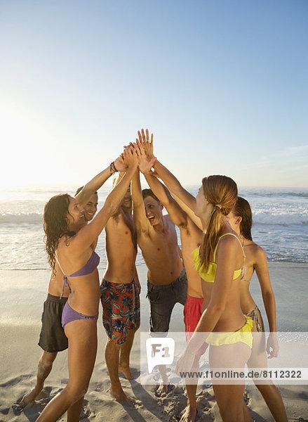 Freunde hoch fiving im Kreis am Strand