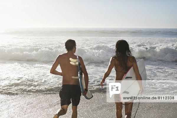 Paar läuft mit Surfbrettern in Richtung Ozean