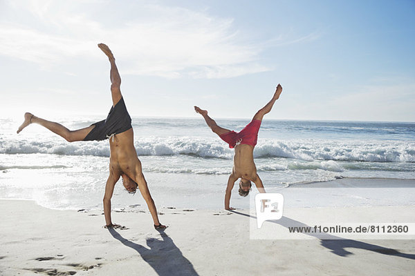 Männer in Badehose beim Handstand am Strand