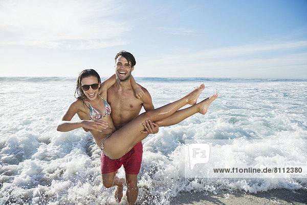 Enthusiastischer Mann mit Frau am Strand