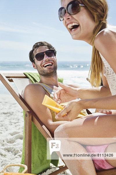 Glückliches Paar mit Sonnencreme am Strand