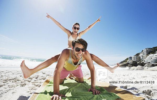 Enthusiastisches Paar Huckepack am Strand