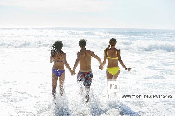 Freunde halten sich an den Händen und rennen ins Meer.