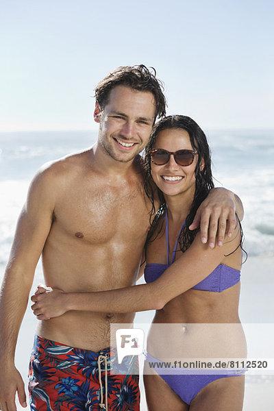 Porträt eines lächelnden Paares  das sich am Strand umarmt.