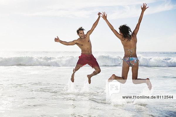 Pärchenspringen mit erhobenen Armen am Strand
