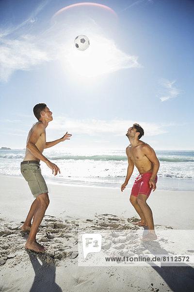 Männer in Badehose auf dem Weg zum Fußball am Strand