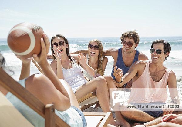 Glückliche Freunde mit Fußball am Strand