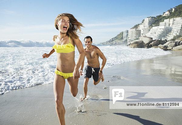 Mann jagt glückliche Frau am Strand