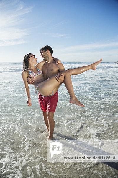 Mann mit Frau in der Meeresbrandung