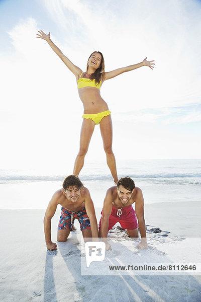 Porträt einer Frau  die auf dem Rücken eines Mannes am Strand steht.