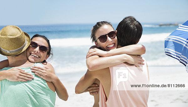 Glückliche Paare umarmen sich am Strand