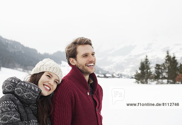 Happy couple in snowy field